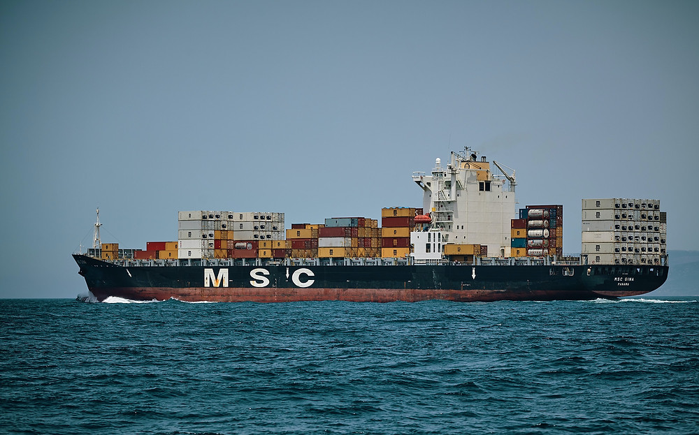 A ship brings containers off the shore