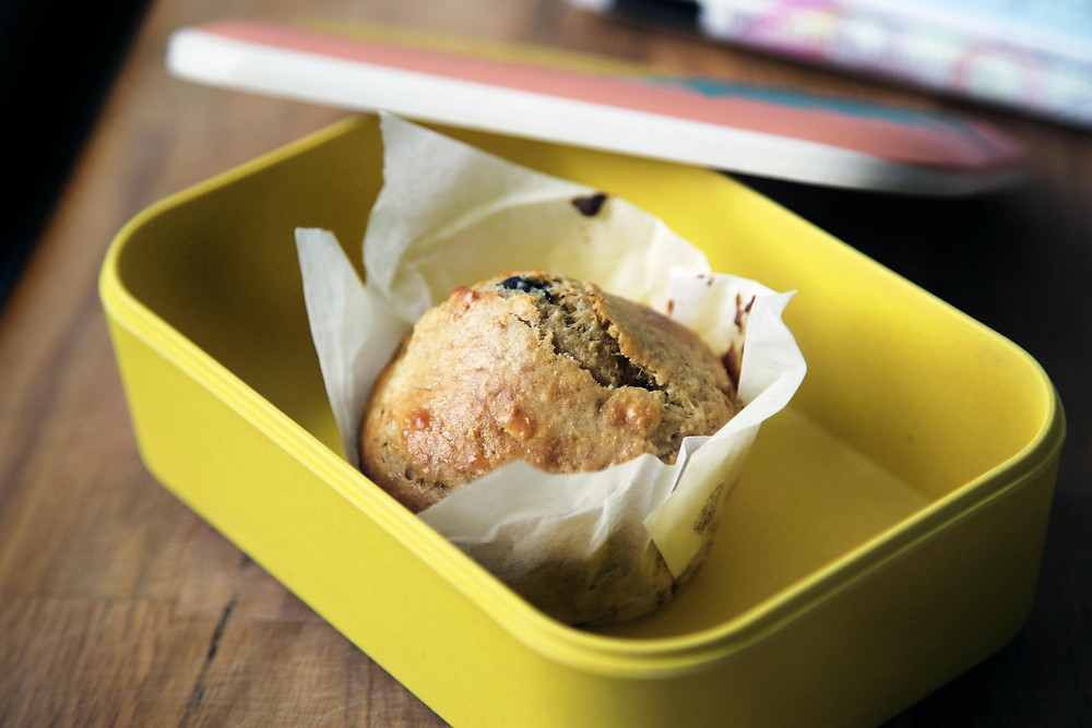 Muffin inside a yellow plastic container