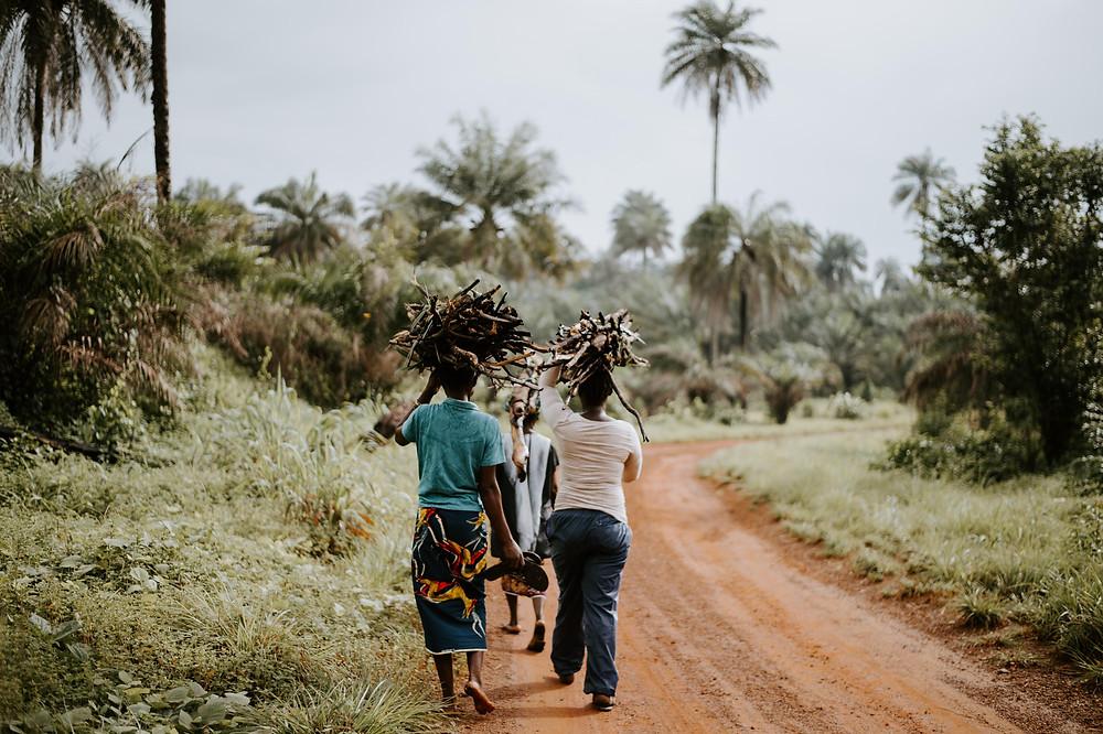 Dua wanita dan seorang anak berjalan di hutan sambil memegang kayu di atas kepala mereka.