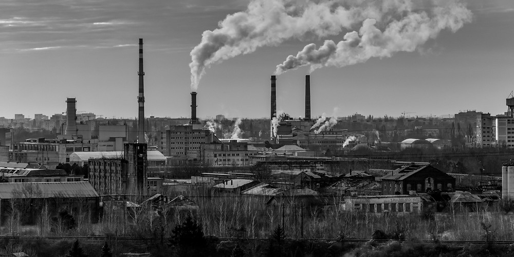 Pabrik-pabrik di pinggiran kota dengan asap yang membumbung tinggi dari lonceng.