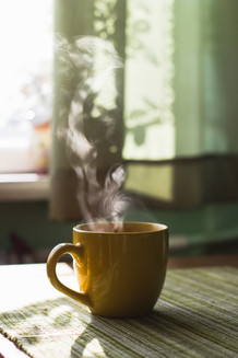 Steam of morning tea above yellow cup on