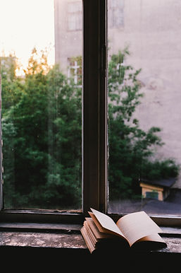 Picture of open window, a desk with a book lying open