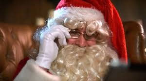 Santa Claus with a big white beard, in a red hood, holding onto his silver spectacles