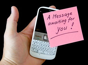 A mobile phone, held in the palm of a hand and a post-it stuck to the screen saying A Message Awaiting You