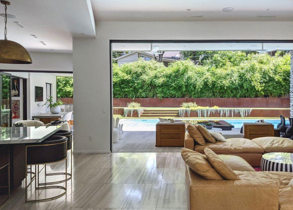 modern-living-room-kitchen-open-space-large-pocketed-slider-windows-biege-sofa-lankerani-architecture