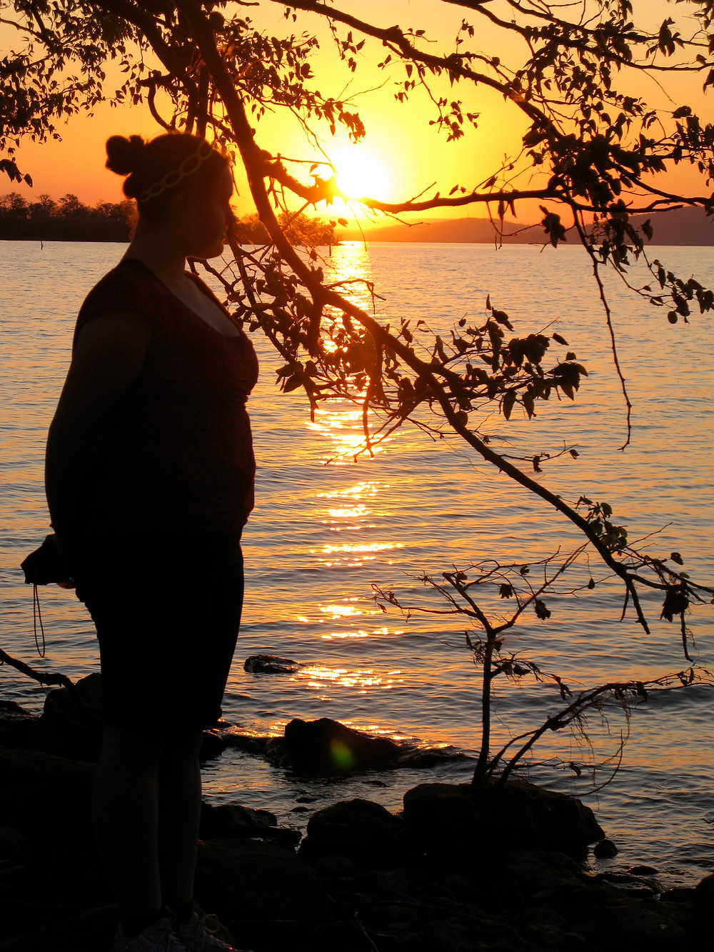 A woman's silhouette in front of a sunset
