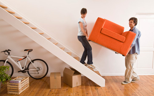 young couple moving into new house carrying a chair upstairs