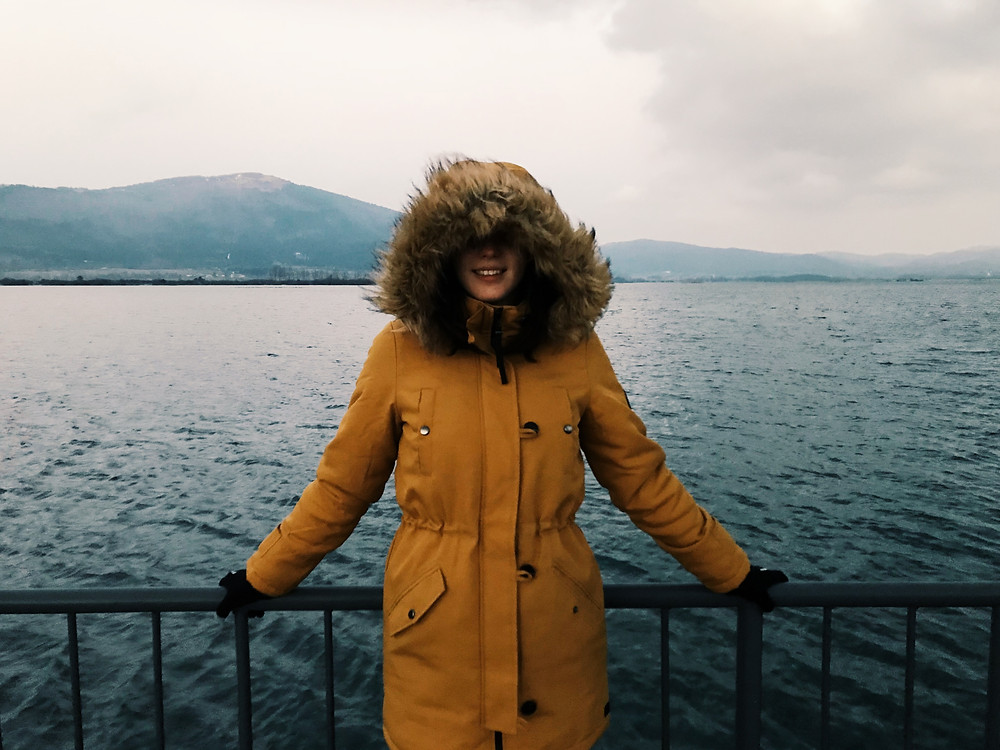 adventurous woman in yellow parka coat out at sea
