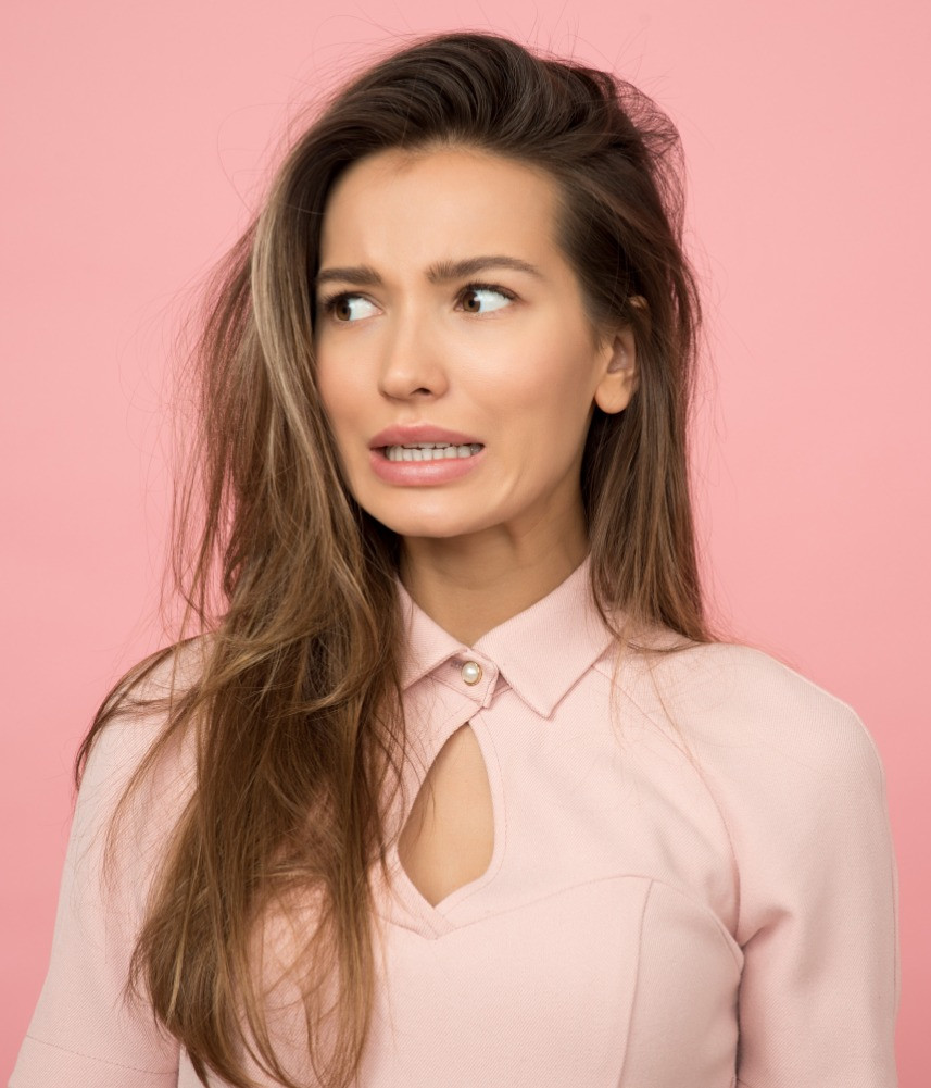 worried looking young attractive woman in pink