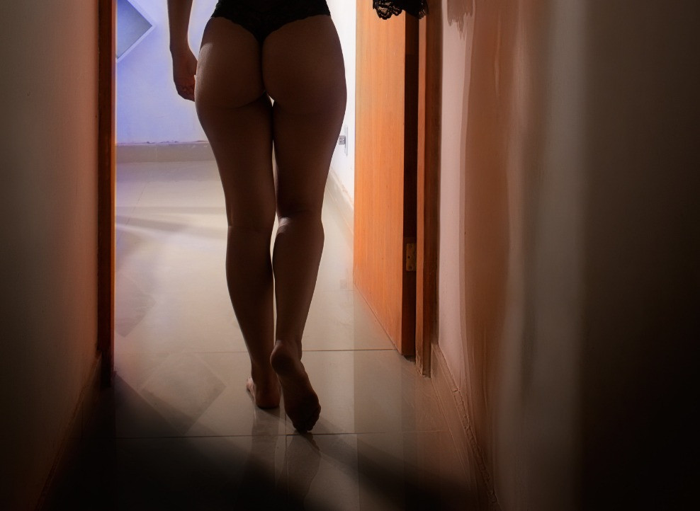 sexy, beautiful woman in a thong walking towards the bedroom