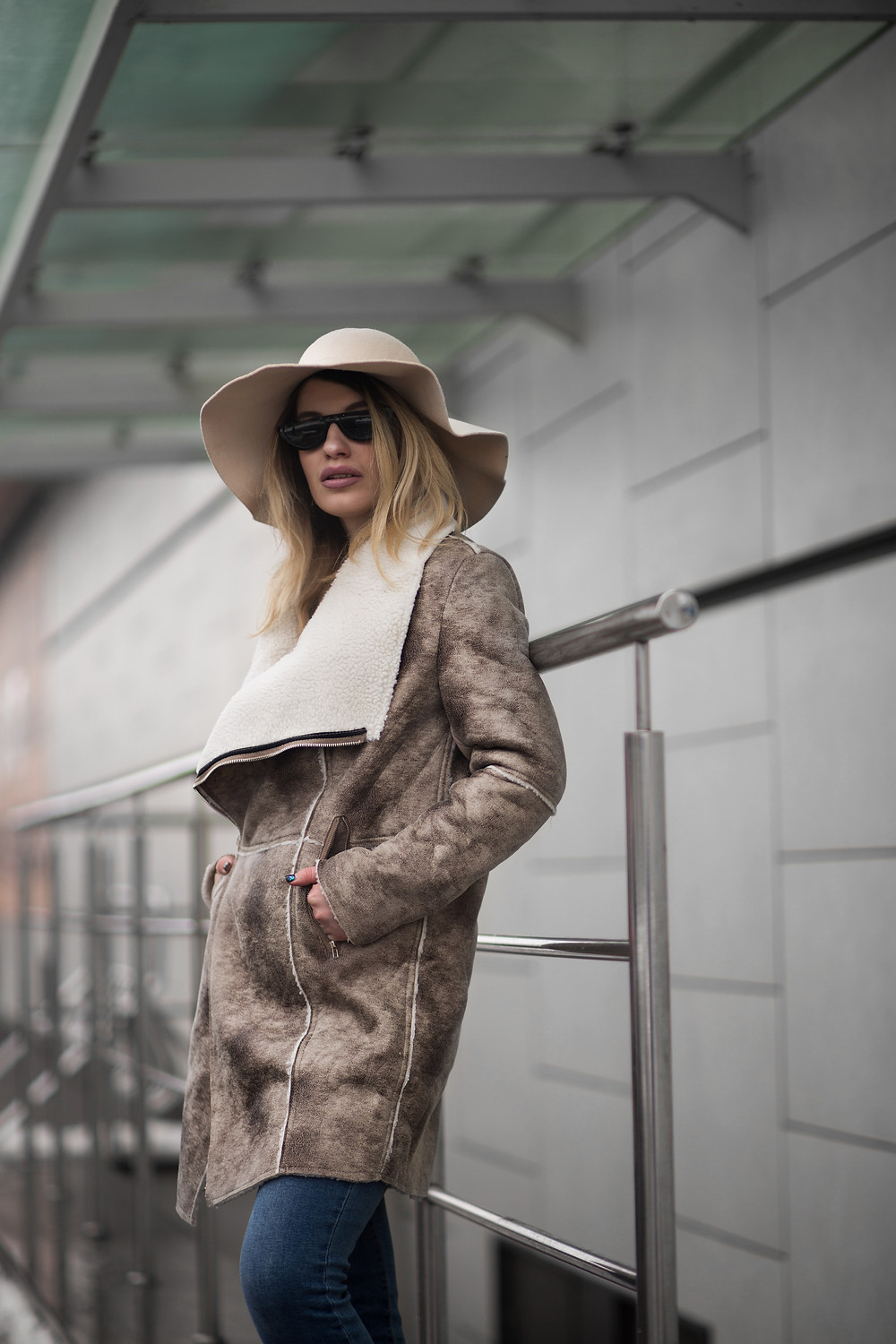 stylish blonder woman in hat and fashionable coat