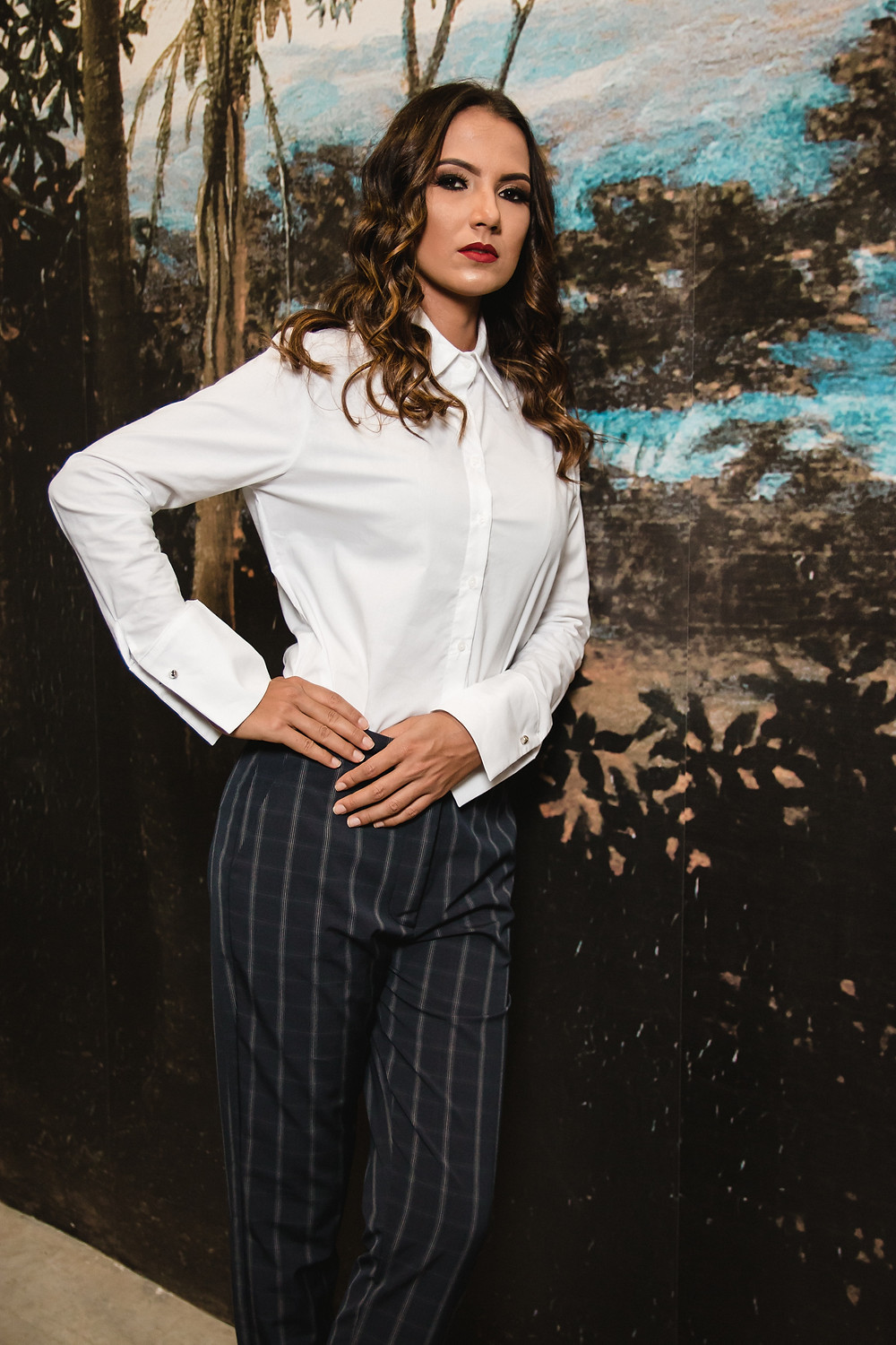 confident woman in suit leans against wall with backdrop