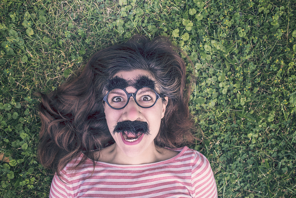 funny, crazy girl with fake nose and mustache on pulling a funny face lying in the grass