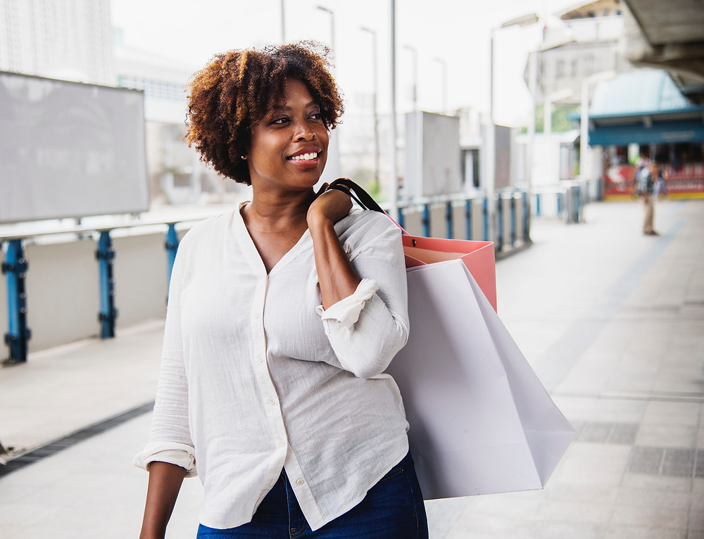 happy woman walks along with clothes shopping