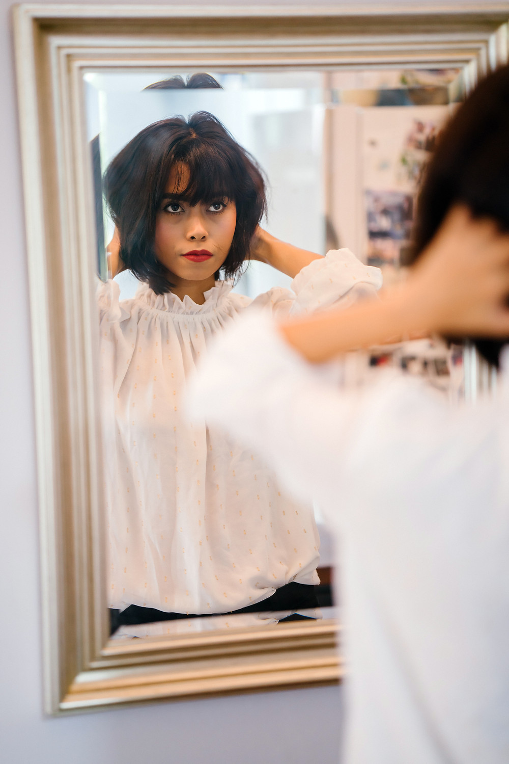 confident woman looks in mirror at reflection, checks hair