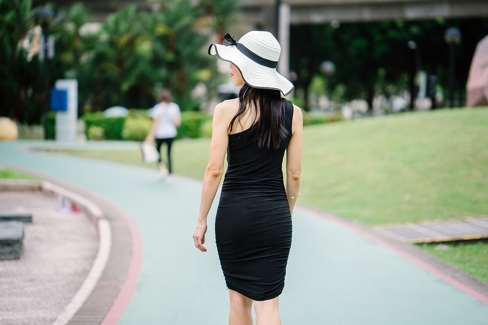 stylish woman in a beautiful black dress and amazing white hat