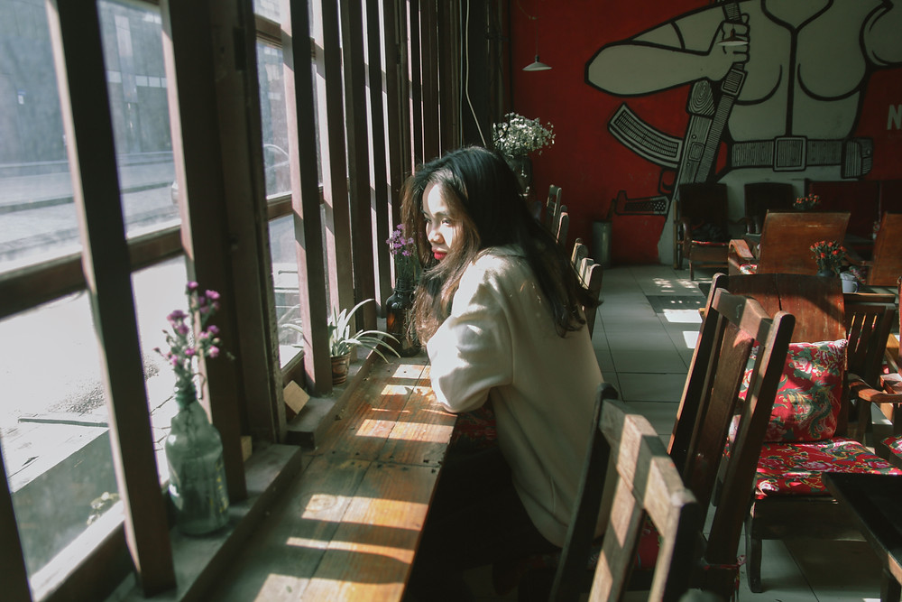 girl sitting alone in a cafe by the window looking out onto the street