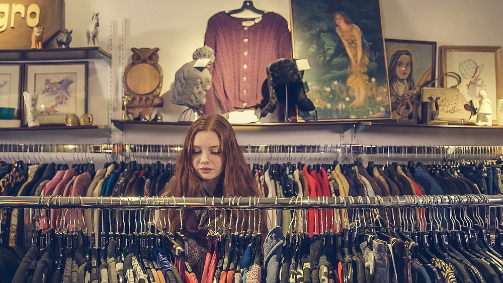 hipster young woman shops in charity store