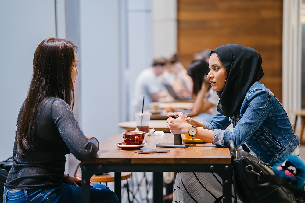 two girls talking and having a coffee in a chill cafe