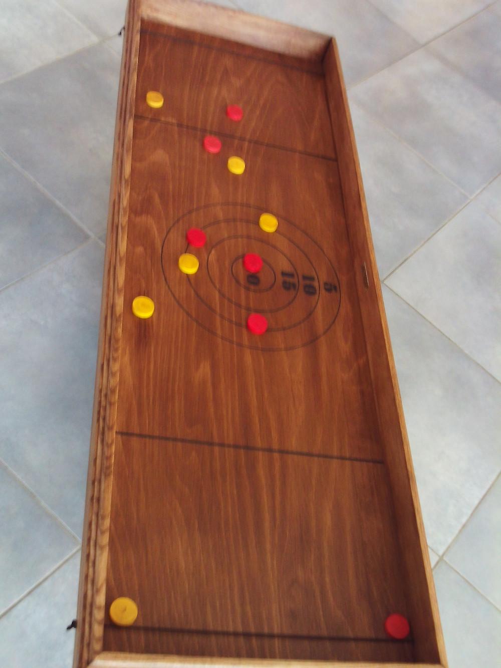 Lancez vos palets en arrière pour les faire rebondir sur l'élastique et atteindre le centre de la cible pour marquer le plus possible de points.  Dimensions : 122 x 41 cm. Nombre de joueurs : 2 et +. A partir de 4 ans.