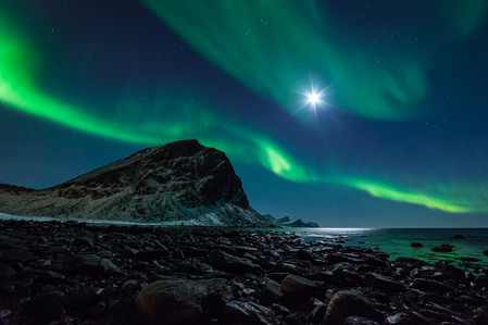 Pleine lune et aurores boréales sur plage de galets en Norvège