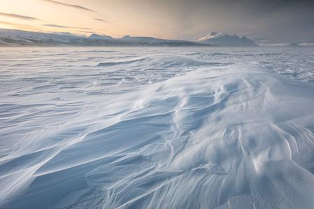 Neige accumulée par le vent sur le lac en laponie suédoise