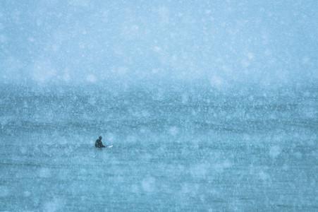 Surfeur sur sa planche dans les fjords sous la neige