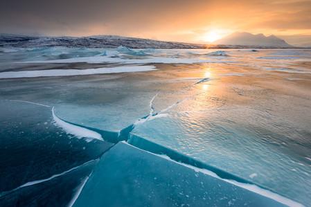 Coucher de soleil sur le lac glacé dans le parc national Stora Sjofallet en Suède
