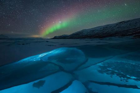 Aurore boréale au desus d'un lac de glace éclairé à la frontale en Laponie