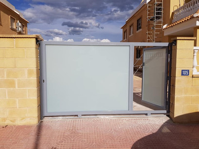 Gray & Glass sliding Gate with Access Door The Gate & Garage Door Copany