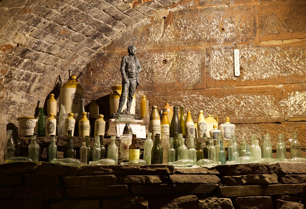 Found bottles and a statue of Joseph Williamson displayed in one of the re-excavated tunnels