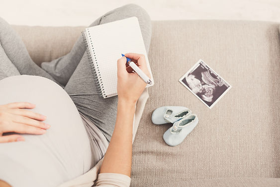 Canva - Pregnant woman writing names for