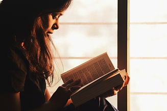 woman-reading-a-book-beside-the-window-1