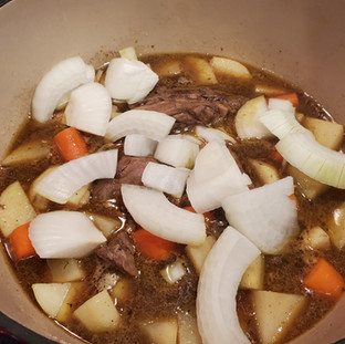 Bring back to a simmer, adding in the onions.