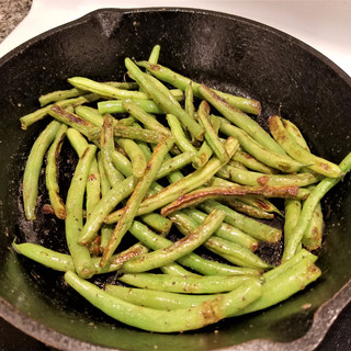 Stir-fry the green beans 8 minutes or so in the oil until they begin to char a little bit, then season them very lightly with salt if you like.