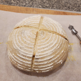 Score the bread deeply in a cross pattern with a lame or a very sharp knife. This is best done swiftly with confident force.
