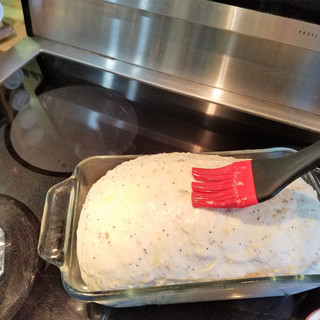 After the dough has risen 1/2 inch or so above the rim of your loaf pan,remove the plastic wrap,gently brush the top with melted butter.