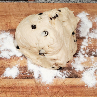 Scrape the dough from the mixer bowl onto the prepared board.