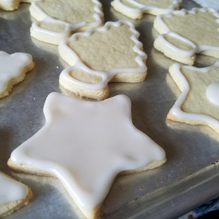 Thin some of the icing to a pourable consistency and use a small spoon or the tines of a small fork to add the icing to the cookies.