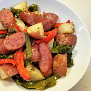 Roasted potatoes peppers and turkey sausage on collard green ribbons.