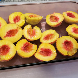 Cut and remove the pits from the peaches then brush them all over with olive oil.