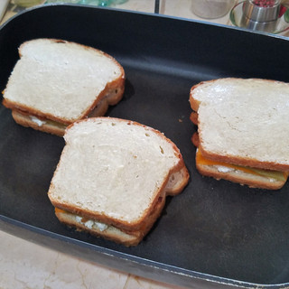 Top the bacon with another slice of cheddar then spread the rest of the cream cheese of the top slices of bread evenly and place it butter side up on the sandwiches.