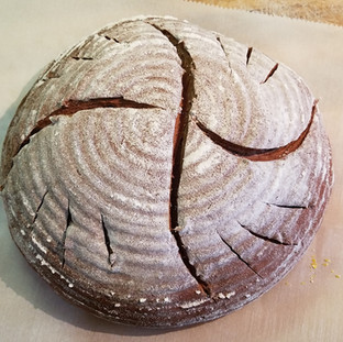 Put a cast iron dutch oven in your oven and begin heating it to 450 degrees for at least 30 minutes.When the dough has risen properly, roll your loaf out of the basket and onto a piece of super handy parchment paper that you have sprinkled with corn meal or polenta and score as you like.