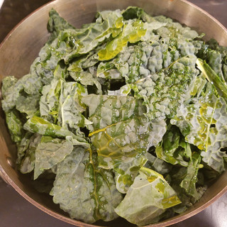 Add some olive oil, garlic and red pepper flakes to a large skillet with a lid and sautee them for 30 seconds before adding the kale a little more olive oil and some chicken stock. Cover and reduce heat, simmering for 8-10 minutes.