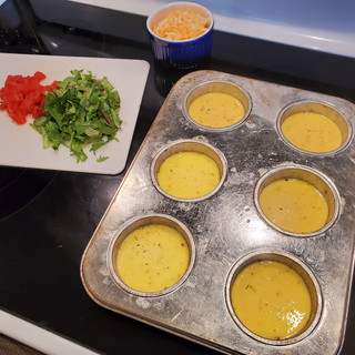 Spray oil a large muffin pan then fill each cup half full with the egg mixture.