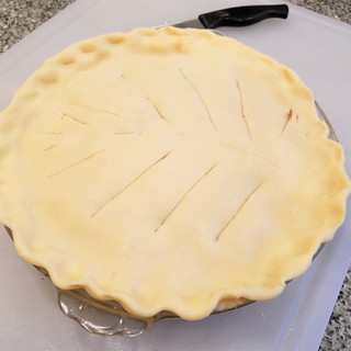Roll out the second sheet of pie crust and lay it accross the pie folding the edges under the bottom crust to seal. Score the pie decoratively to let steam escape as it bakes.