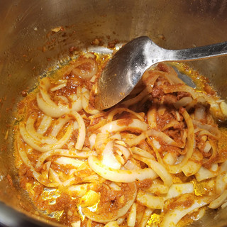 Stir-fry the onions and garlic in the curry paste until golden and fragrant.