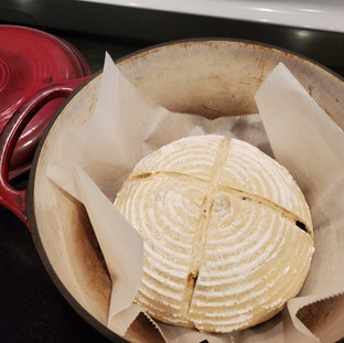 Carefully remove the Dutch oven from the hot oven and remove the lid. Place the loaf inside using the paper then cover and place the Dutch oven back inside the hot oven.