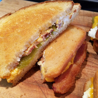 Remove the sandwiches from the skillet and cut in half to serve.