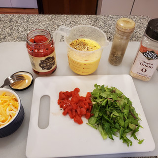 Preheat your oven to 400 degrees. Gather your ingredients, stir the onion and seasonings into the eggs then chop up some bell pepper and greens.